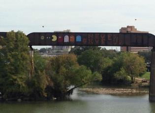 """Never Give Up"" graffiti mural on the Austin Railroad Graffiti Bridge over Lady Bird Lake"